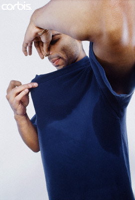Man in Sweaty Shirt Holding Nose
